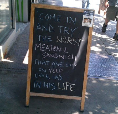 A humorous chalkboard a restaurant put up in response to a negative Yelp review